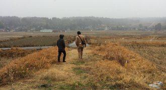 農地を探して歩く二人の男性