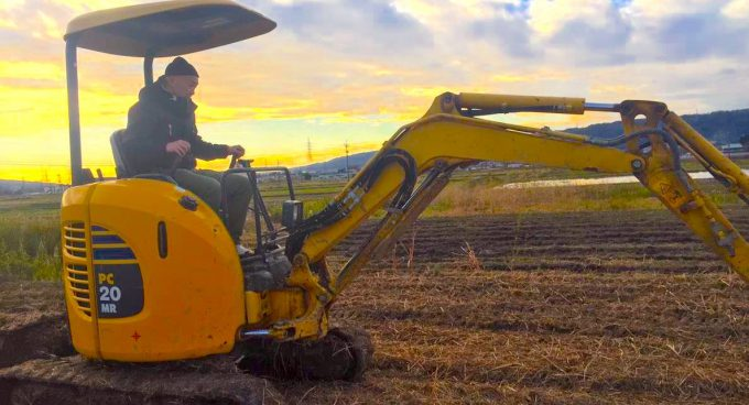 夕陽の中、耕作するパワーショベル