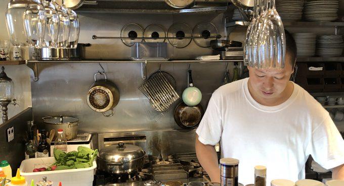 金沢レストランドゥブの店内で料理する柏オーナー