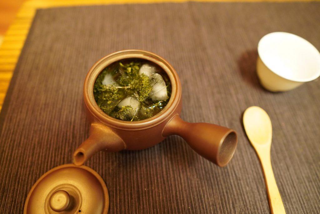 日本酒カクテル作りに茶葉と氷入り急須に酒を注ぐ